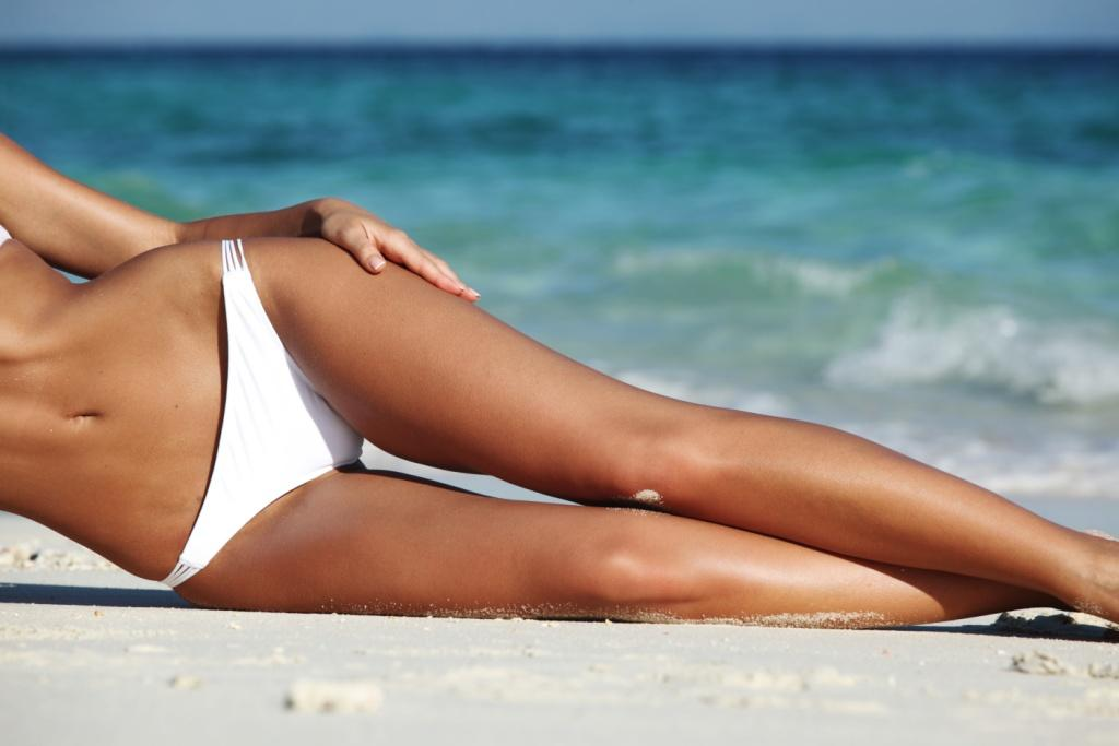 Woman on beach. Spray tan. Tanning.